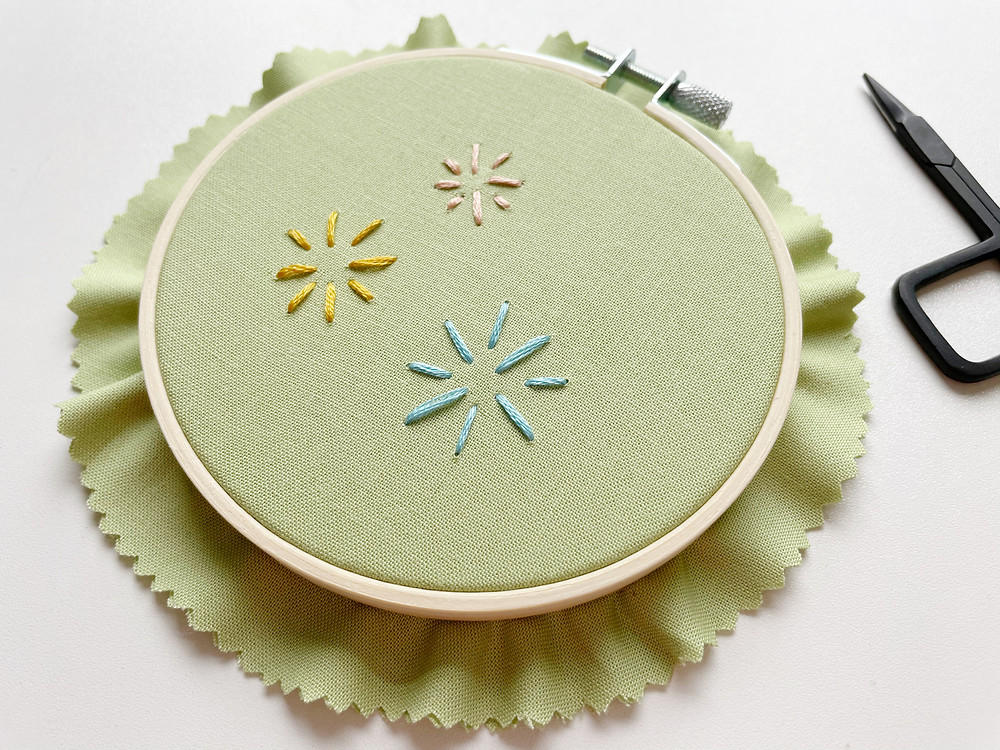 A photo of a light green embroidery hoop with yellow, pink, and blue lines stitched on top.
