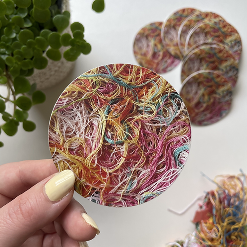 Hope holds up a round sticker with embroidery floss scattered about the surface in pinks, yellows, blues, and other colors.