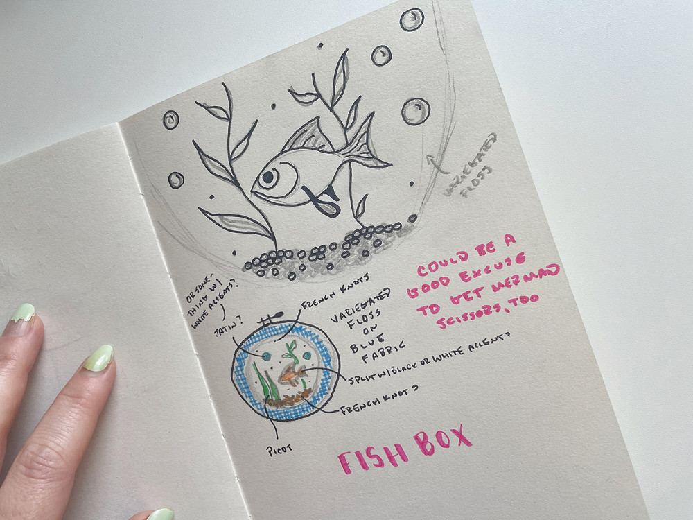 Photo of a sketchbook with rough drawings of a goldfish and notes.