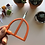 Hope is holding up a pair of orange embroidery scissors with large handles.