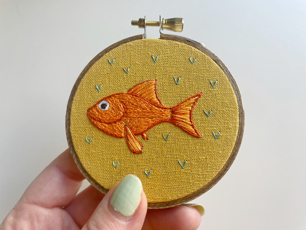 A photo of a goldfish stitched onto mustard fabric and surrounded by blue accents.