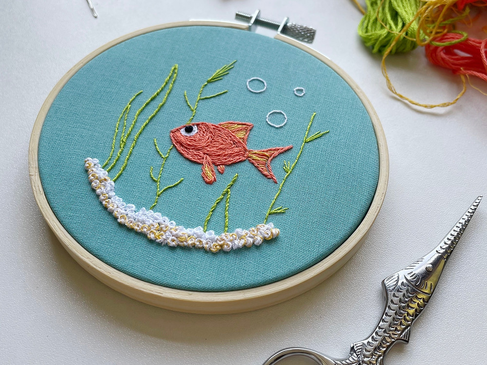 Picture of an embroidery hoop with a goldfish stitched onto blue fabric and surrounded by bubbles, plants, and aquarium rocks.