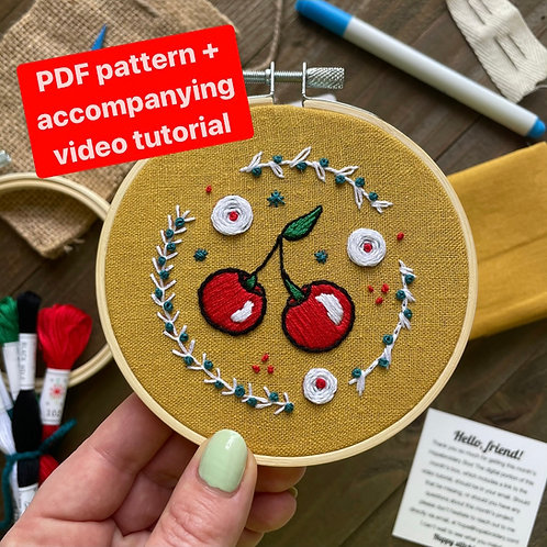 Hope holds up an embroidery hoop with bright red cherries stitched onto mustard fabric.