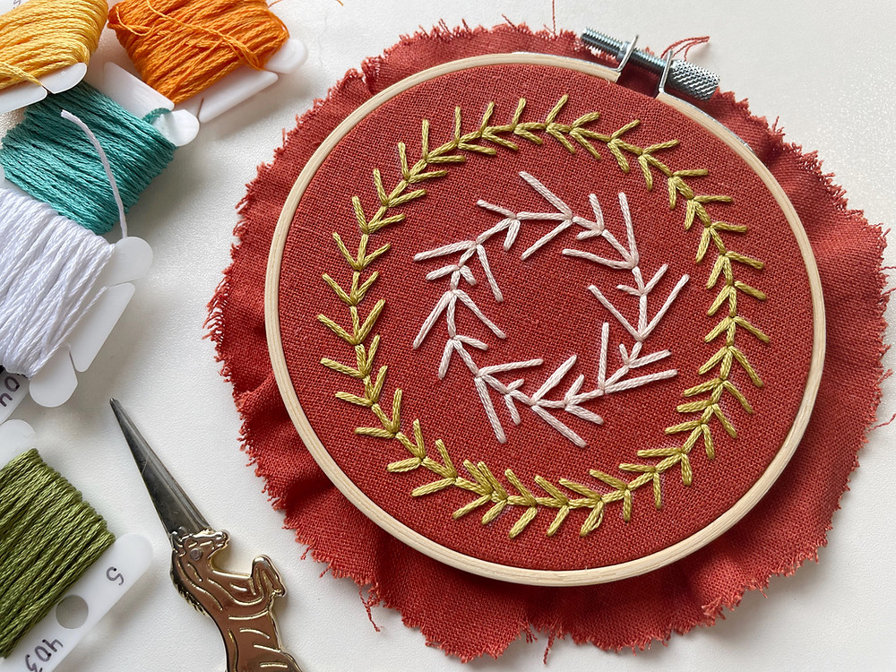 Photo of an embroidery hoop with vines stitched in green and pink onto dark orange fabric.