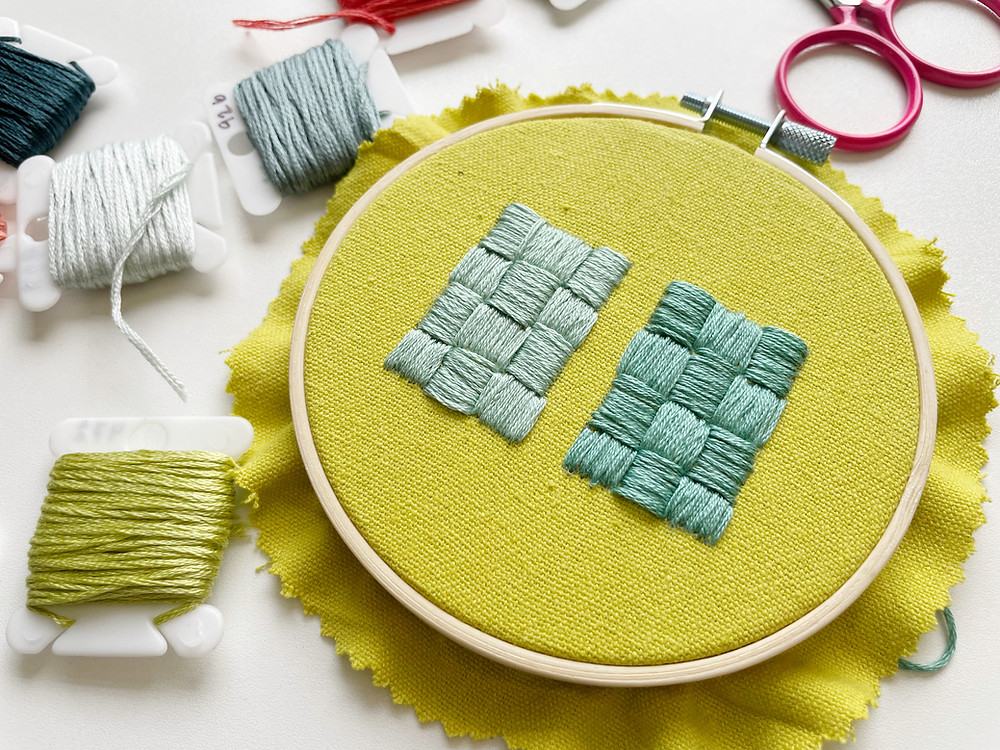 A photo of an embroidery hoop with two blue rectangles stitched onto bright green fabric and surrounded by embroidery floss and scissors.