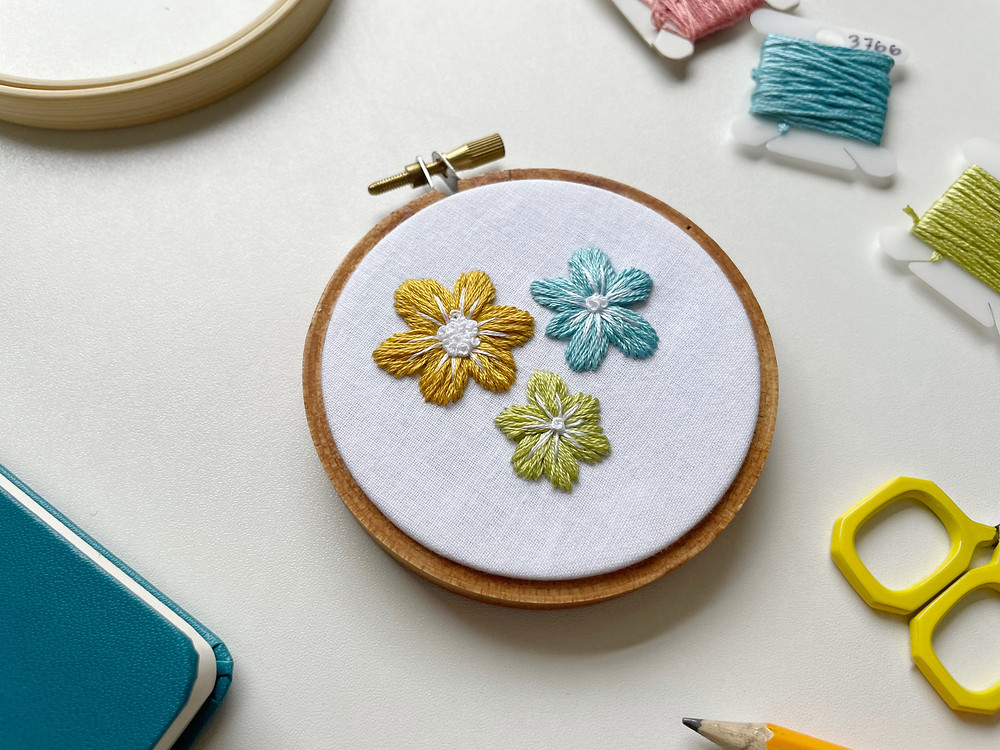A photo of three flowers stitched in yellow, blue, and green floss onto white cotton fabric.
