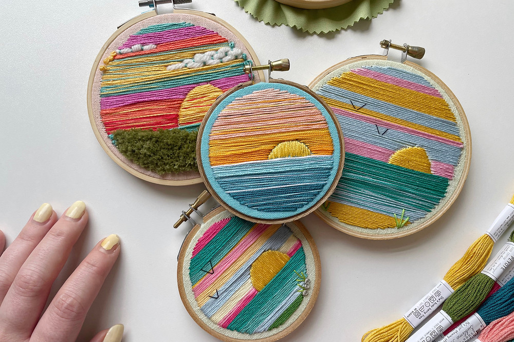 A photo of four embroidery hoops featuring landscapes stitched with vibrant colors.