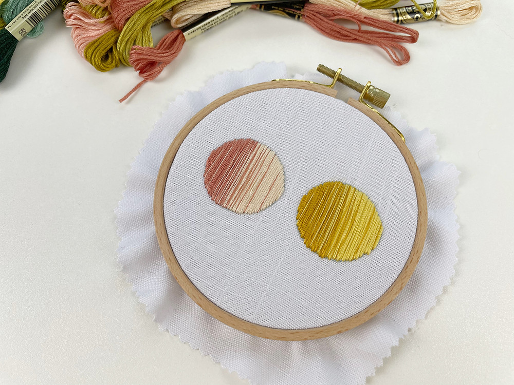 Photo of an embroidery hoop with pink and yellow circles stitched onto white fabric.