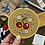 Hope holds up an embroidery hoop with bright red cherries stitched onto mustard fabric, surrounded by florals.