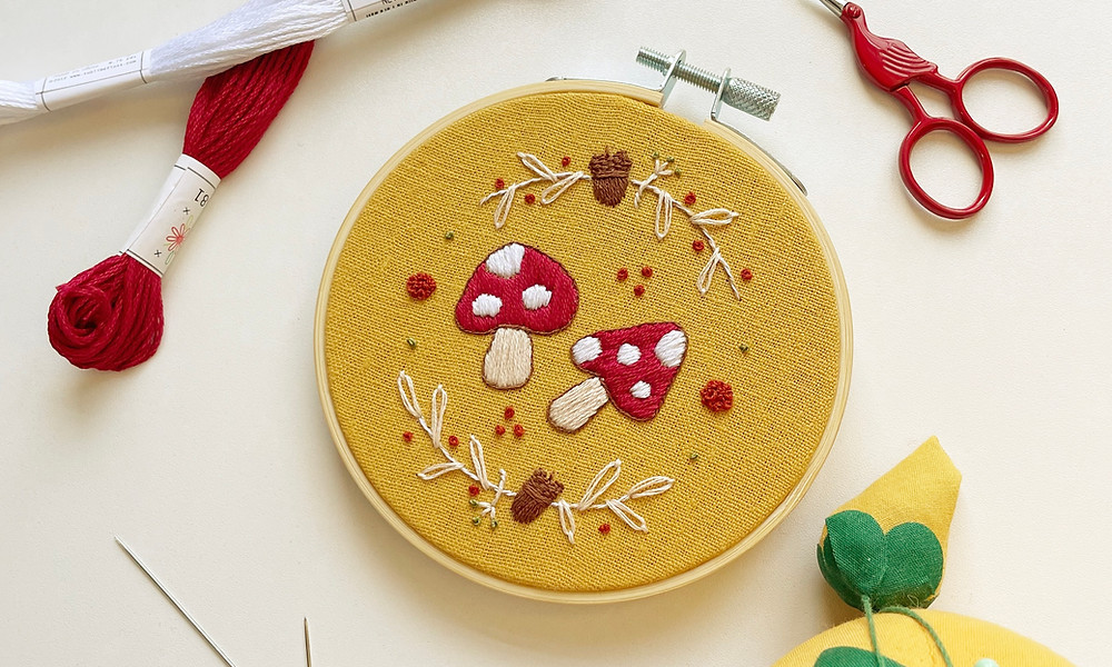 Photo of an embroidery hoop with red and white mushrooms stitched onto mustard fabric, surrounded by acorns and fall-like foliage. The hoop sits on a white surface and is surrounded by red and white embroidery floss, a pair of red stork-shaped embroidery scissors, a yellow and green pin cushion, and needles.