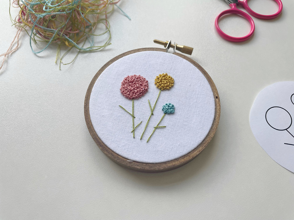 A photo of an embroidery hoop with pink, yellow, and blue flowers stitched onto white fabric.