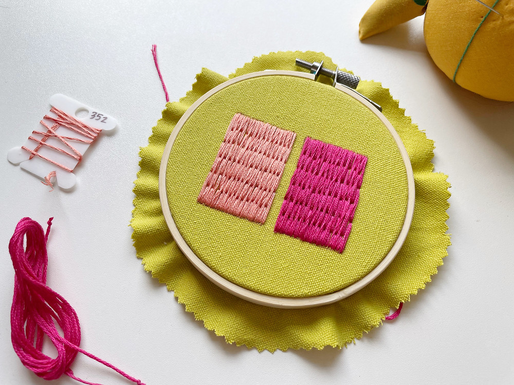 A photo of two pink rectangles stitched onto bright green fabric.