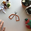 A pair of embroidery scissors with large, orange handles sits open on a white surface.