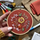 Photo of embroidery hoop with orange, red, yellow, white, blue, and green florals stitched onto dark orange fabric.