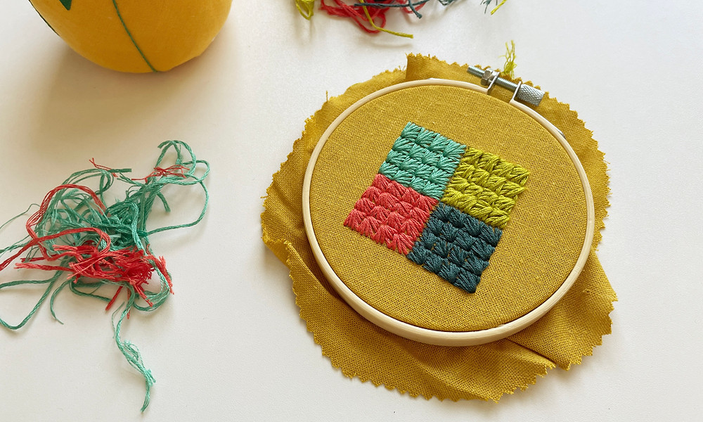 Photo of an embroidery hoop with teal, pink, green, and blue squares stitched onto mustard fabric.