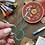 Photo of a pair of long green embroidery scissors, surrounded by various embroidery supplies for a kit.