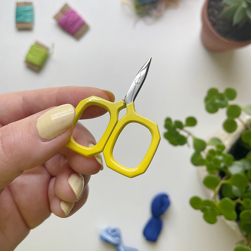 Hope holds up a small pair of yellow embroidery scissors with square handles.