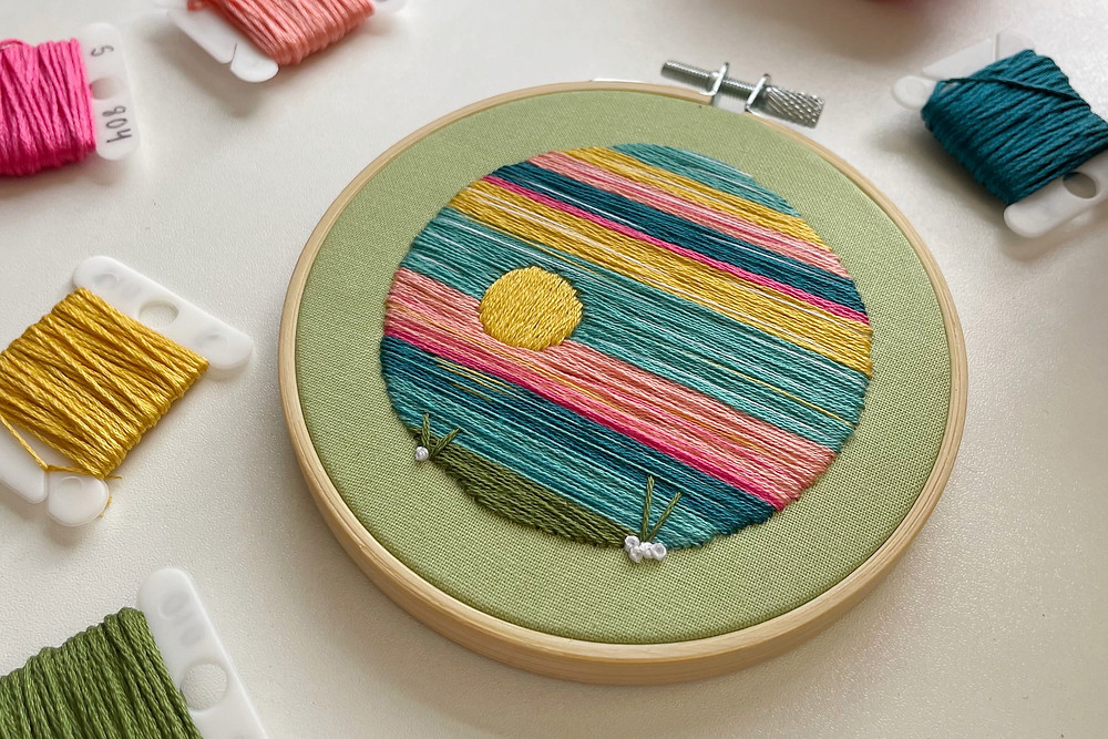 A photo of an embroidery hoop with a landscape stitched in blues, greens, yellows, and pinks onto light green fabric.