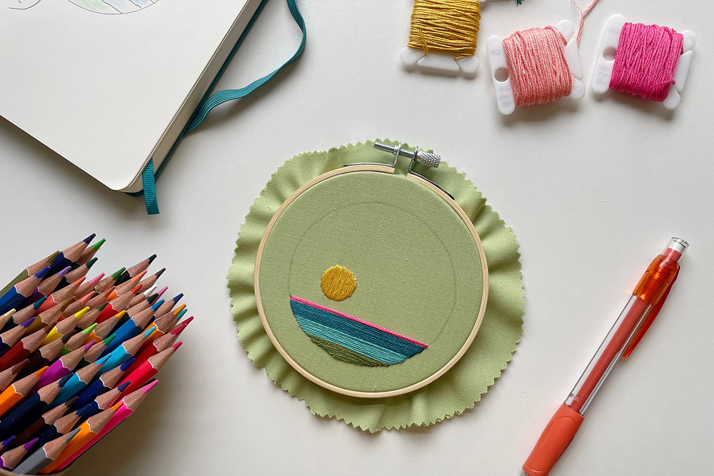 A photo of an unfinished embroidery project surrounded by color pencils, embroidery floss, and a notebook.