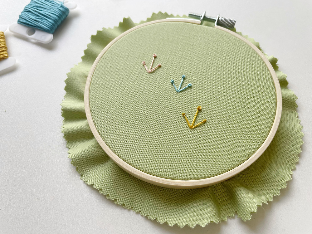 A photo of an embroidery hoop with flower-like designs stitched in pink, blue, and yellow onto green fabric.