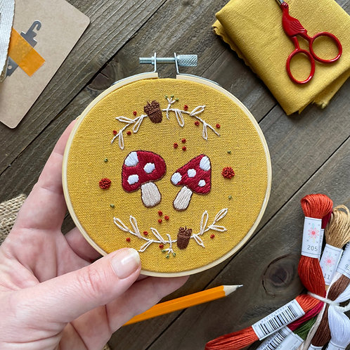Photo of an embroidery hoop with red and white mushrooms stitched onto mustard fabric and surrounded by acorns and fall vines