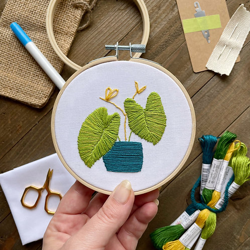 Hope holds up an embroidery hoop with green elephant ear plants stitched in a blue pot on white fabric.