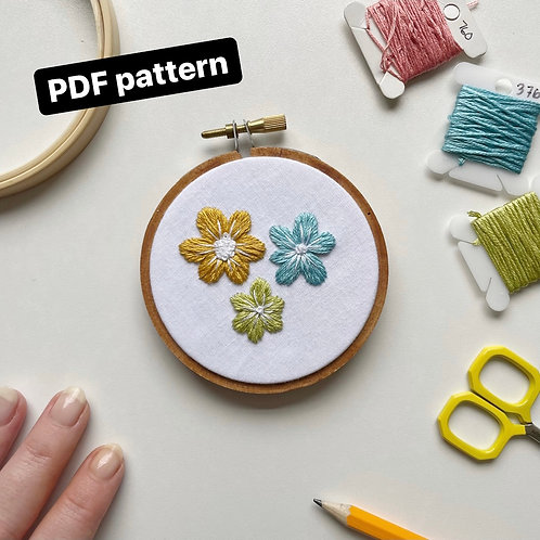 A photo of an embroidery hoop with three flowers stitched in green, blue, and yellow, onto white fabric.