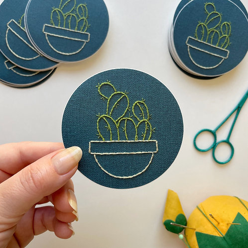 A three inch circular sticker with the photo of an embroidered cactus in green stitched on dark blue fabric.
