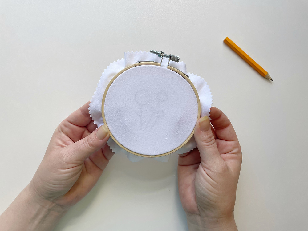Hope holds up an embroidery hoop with white fabric; underneath, you can see she's holding a printed pattern to the fabric.