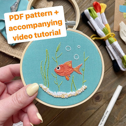 Hope holds up an embroidery hoop with a goldfish stitched onto blue fabric.