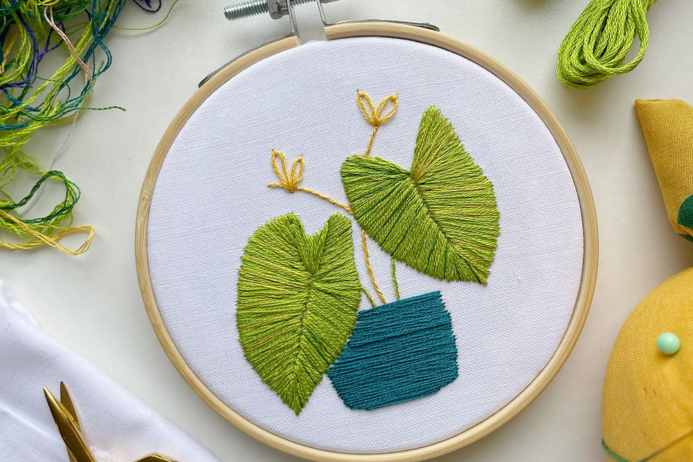 Photo of an embroidery hoop with green elephant ears in a blue pot stitched onto white fabric and surrounded by embroidery supplies.