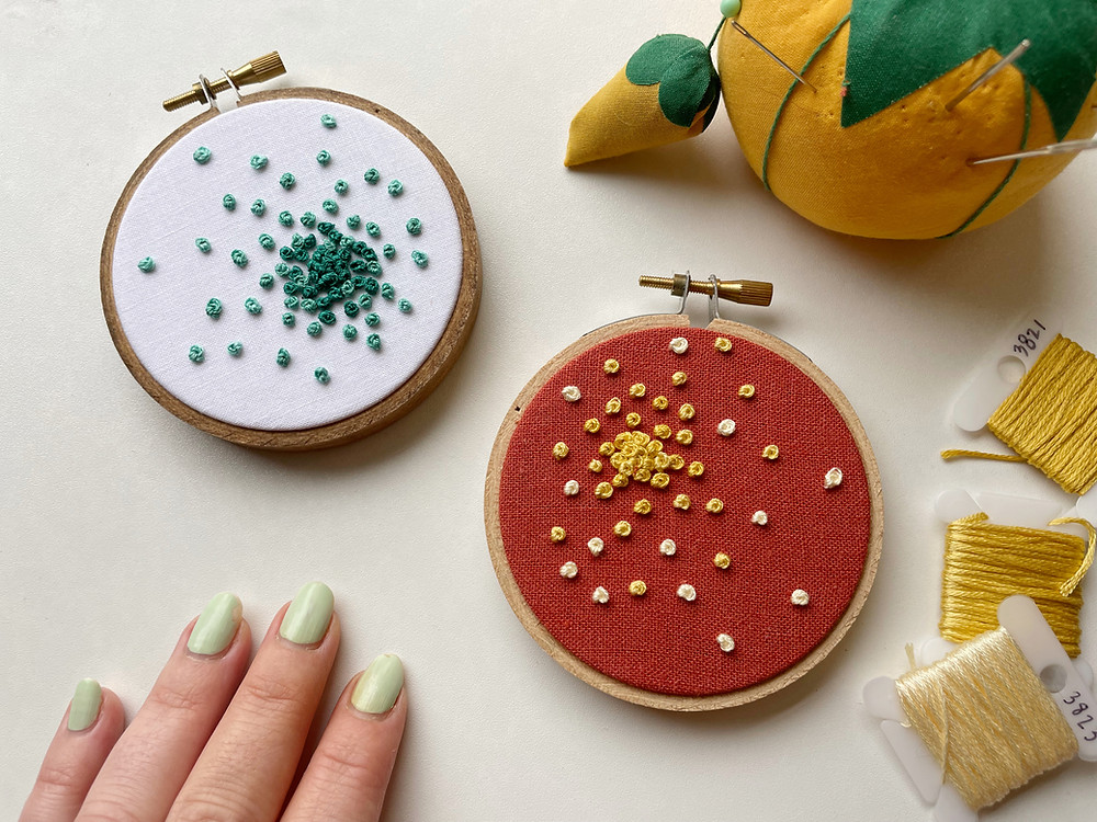 """Photo of two colorful embroidery hoops with French knots in a """"bursting"""" pattern."""