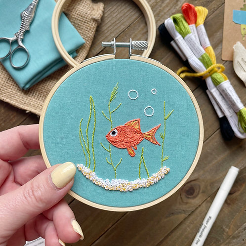 Hope holds up an embroidery hoop with a goldfish stitched onto blue fabric and surrounded by embroidery kit supplies.