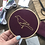 Embroidery hoop with a yellow bird stitched onto dark purple fabric, embroidery supplies in background.