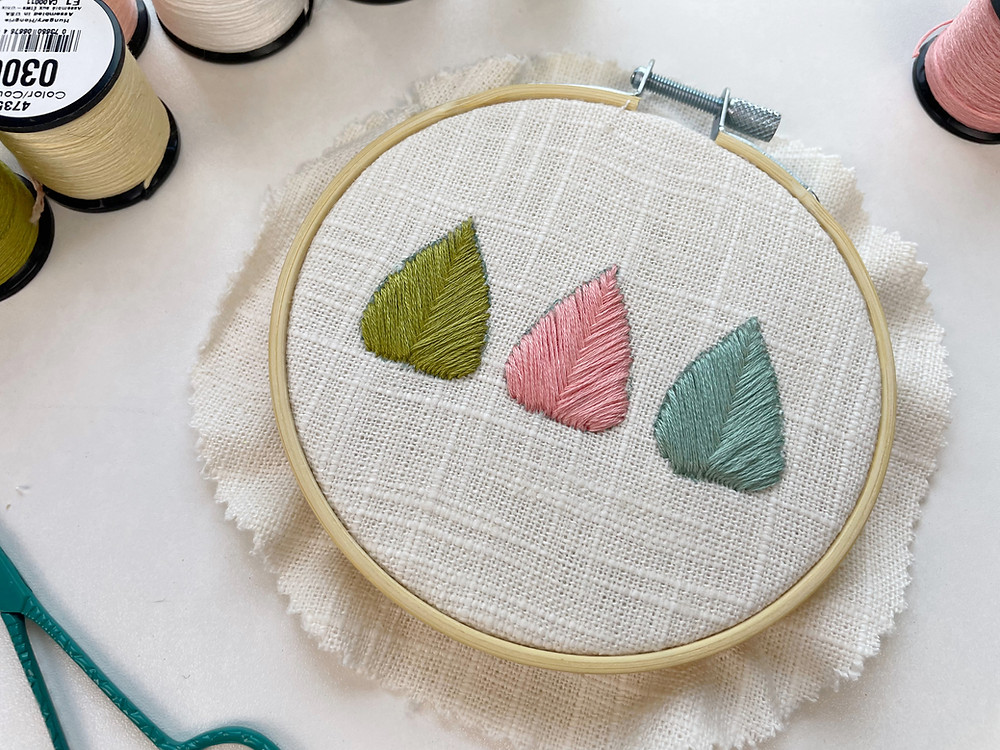 Photo of an embroidery hoop with leaf shapes stitched in green, pink, and blue, on linen fabric using fishbone stitch for hand embroidery.
