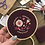 Embroidery hoop with flowers stitched in different shades of pink onto dark purple fabric.