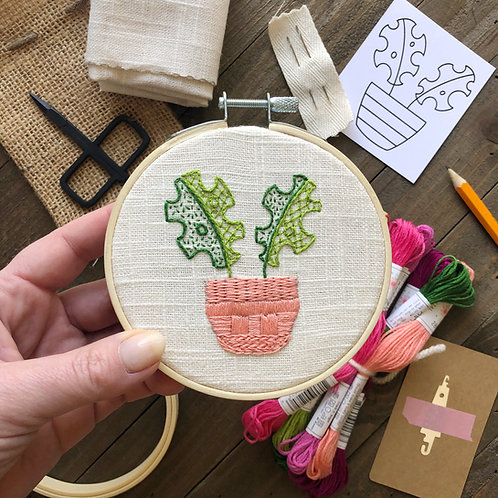 Embroidery hoop with a potted monstera plant stitched in pink and green on white fabric, surrounded by kit supplies.
