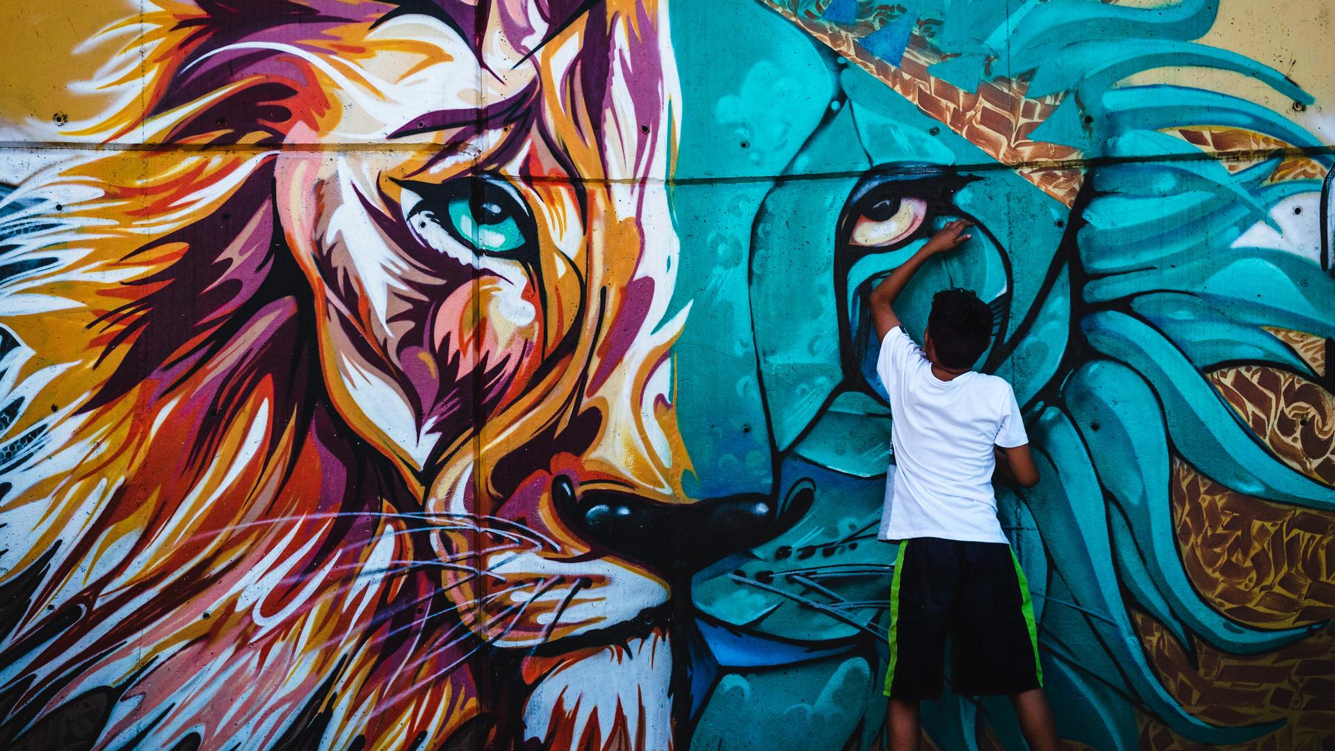 Young boy touching a graffiti lion