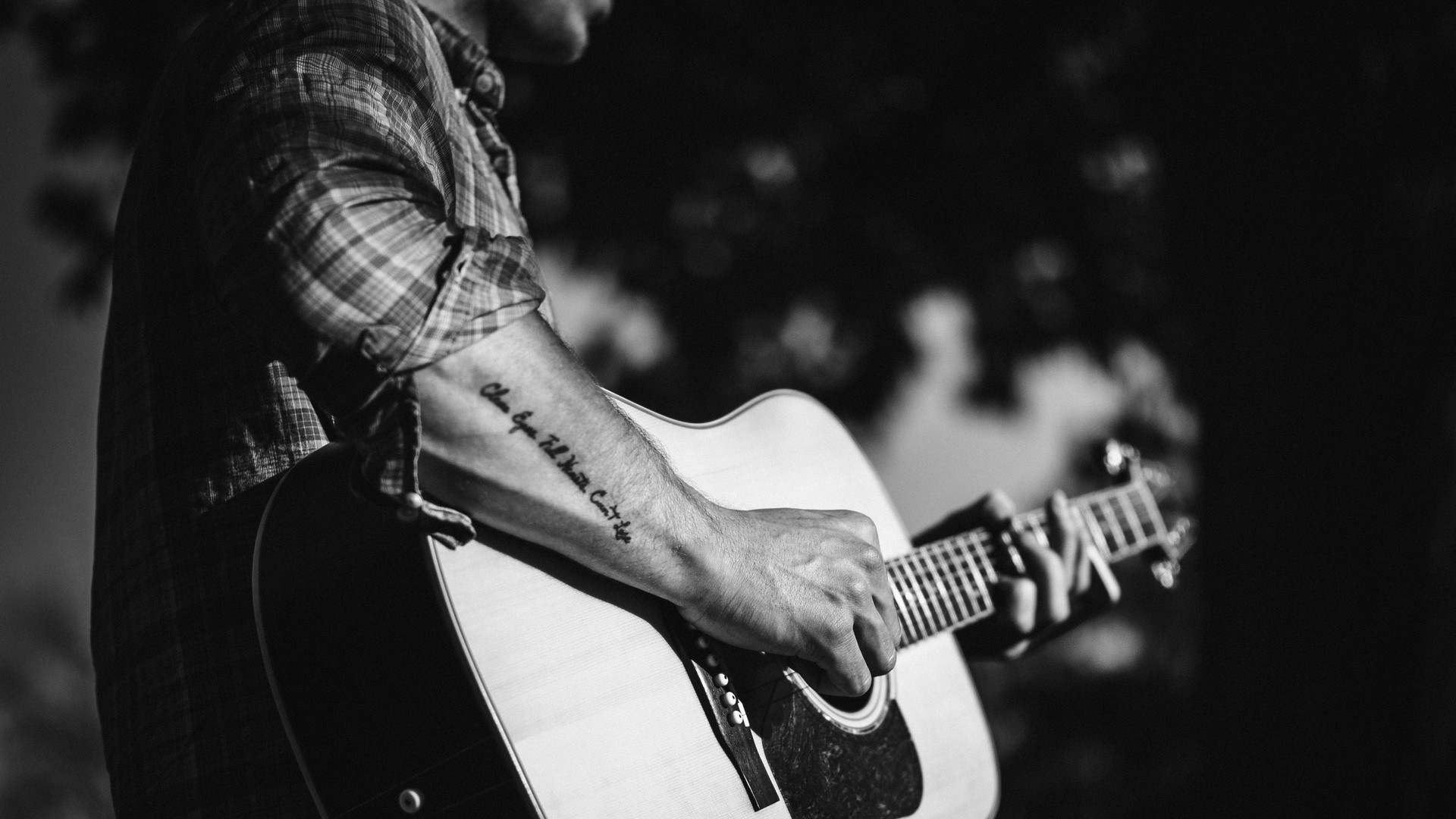 man playing the guitar in black and white