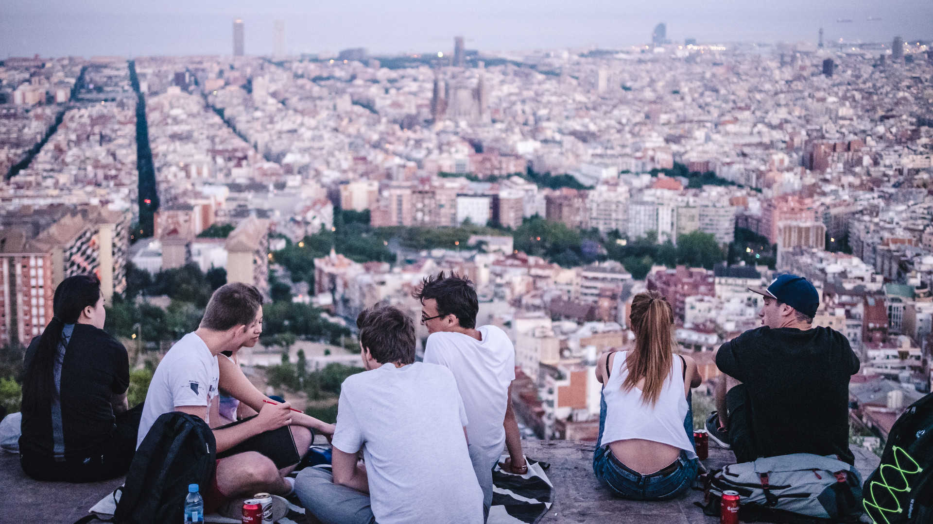 Young people enjoying the view over Barcelona at dusk with pink sky