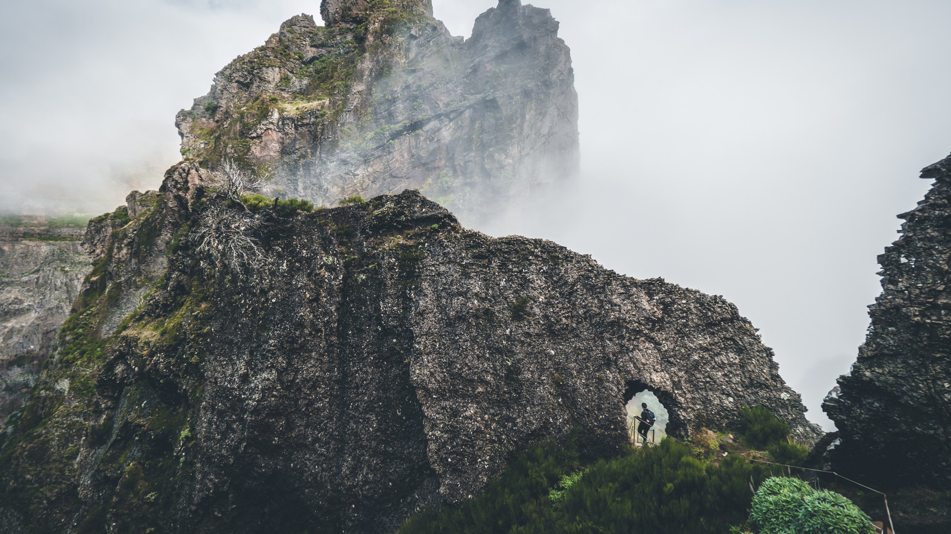 Person walking through a mountain formation in the clouds
