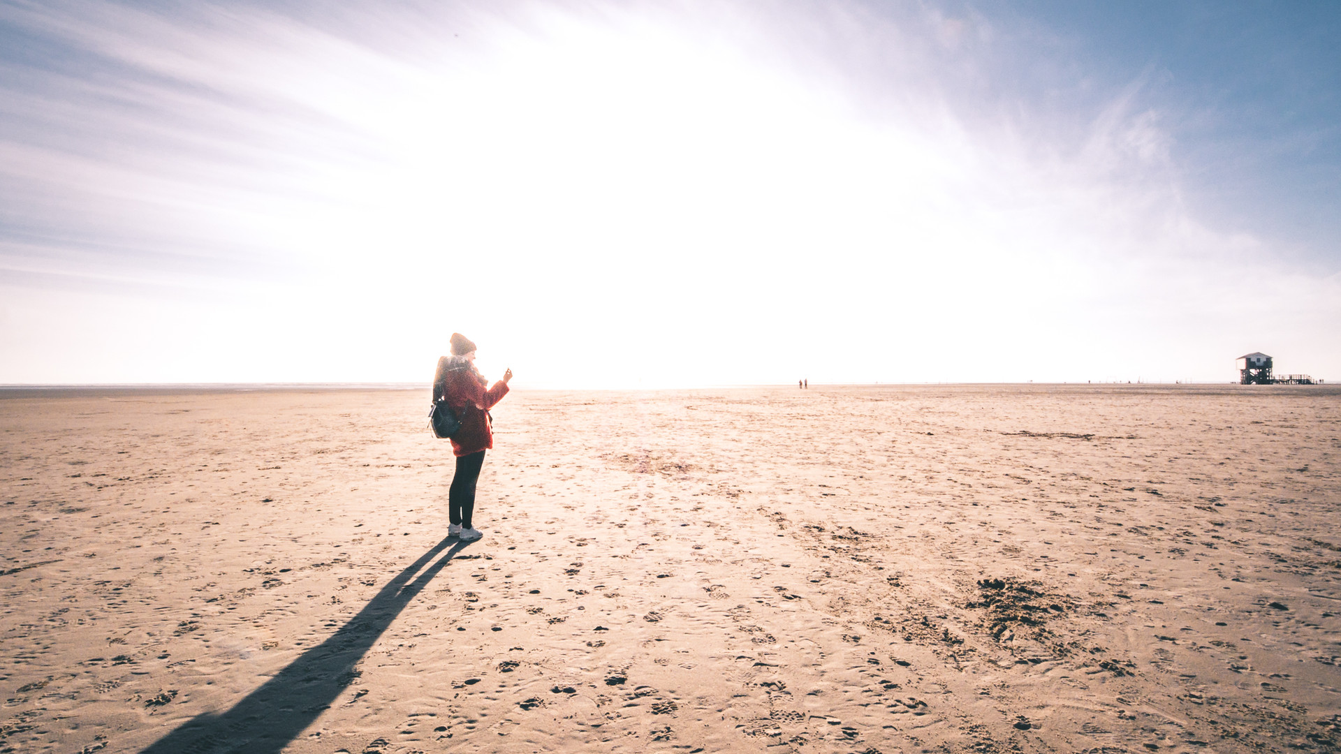 Young woman standing at the beach with frontal sunlight in winter