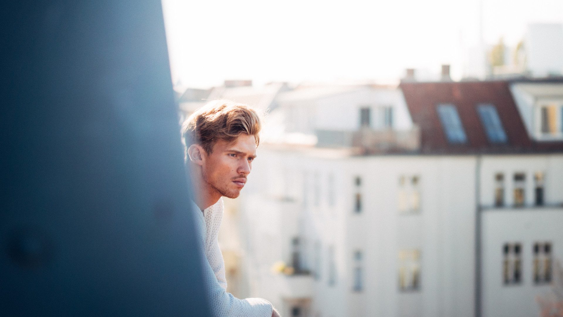 Young man looking out from a balcony in Berlin
