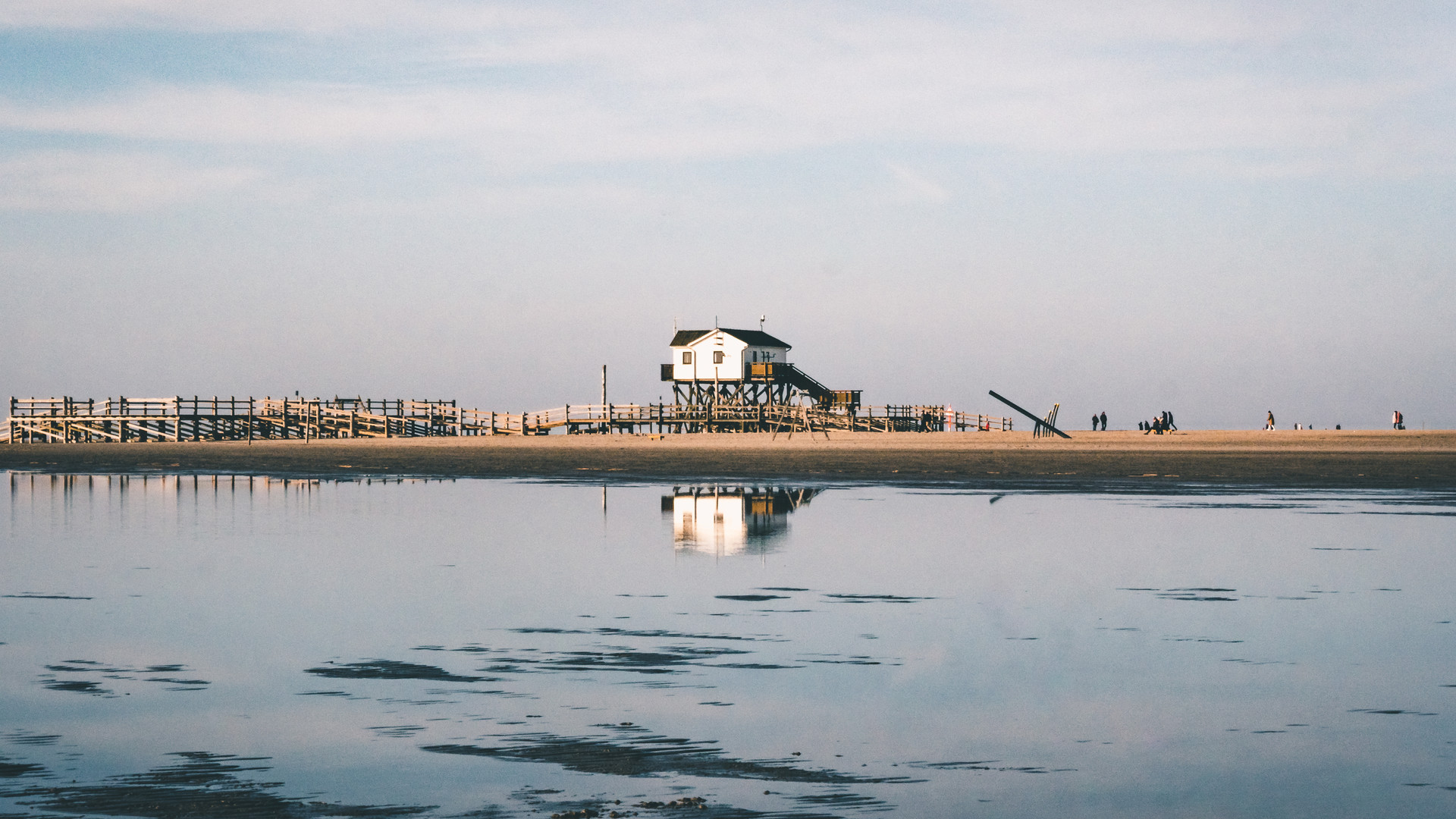 House and reflection in still water at the beach in Germany