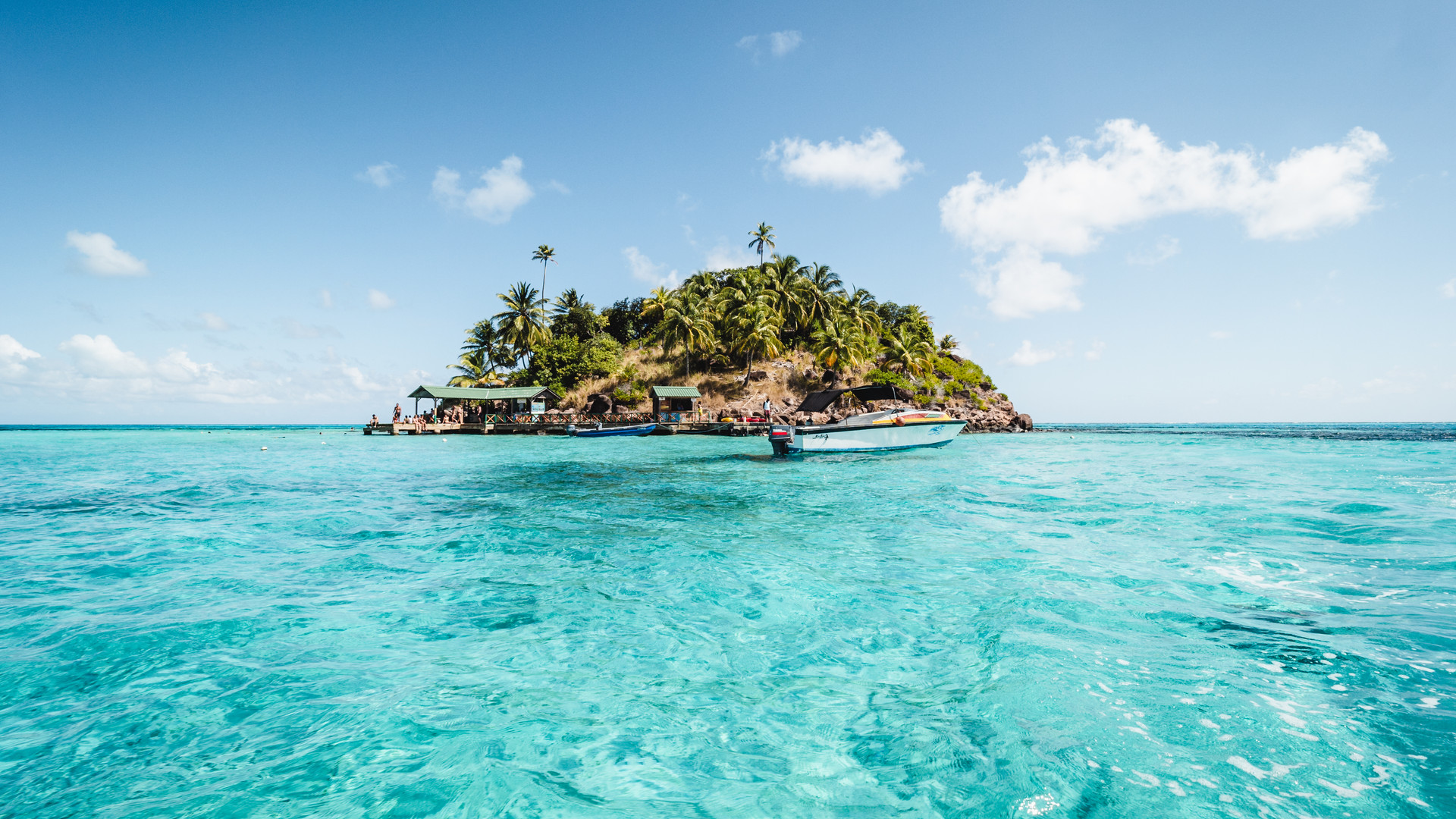 Panoramic view of a tropical island in the sun and crystal clear water