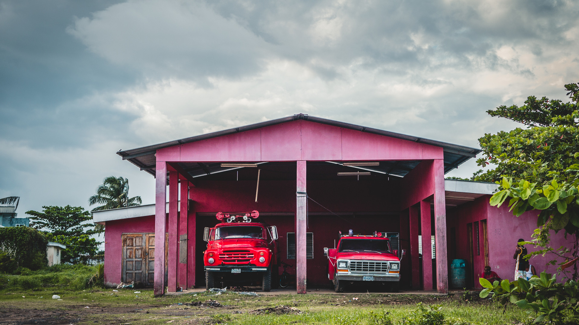 Old firetrucks in a rouge house under dark and cloudy sky
