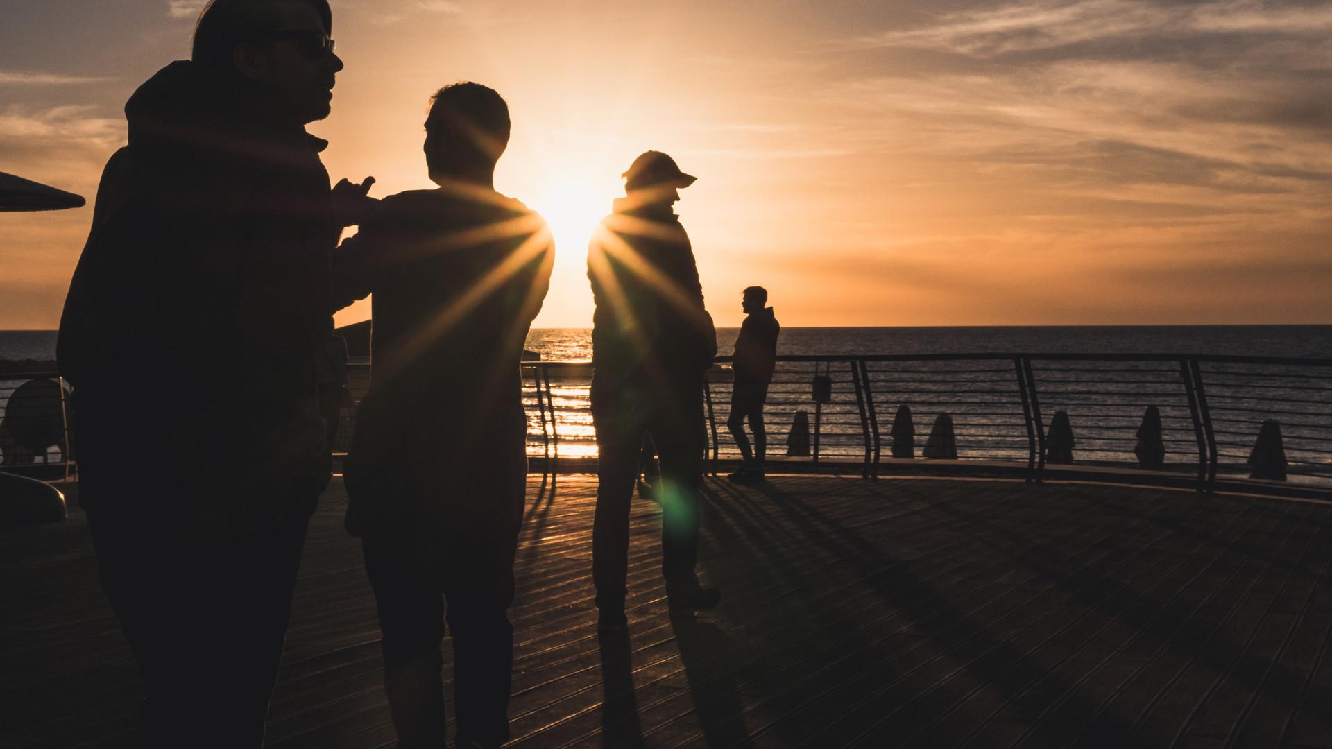 Men exploring the beach at sunset