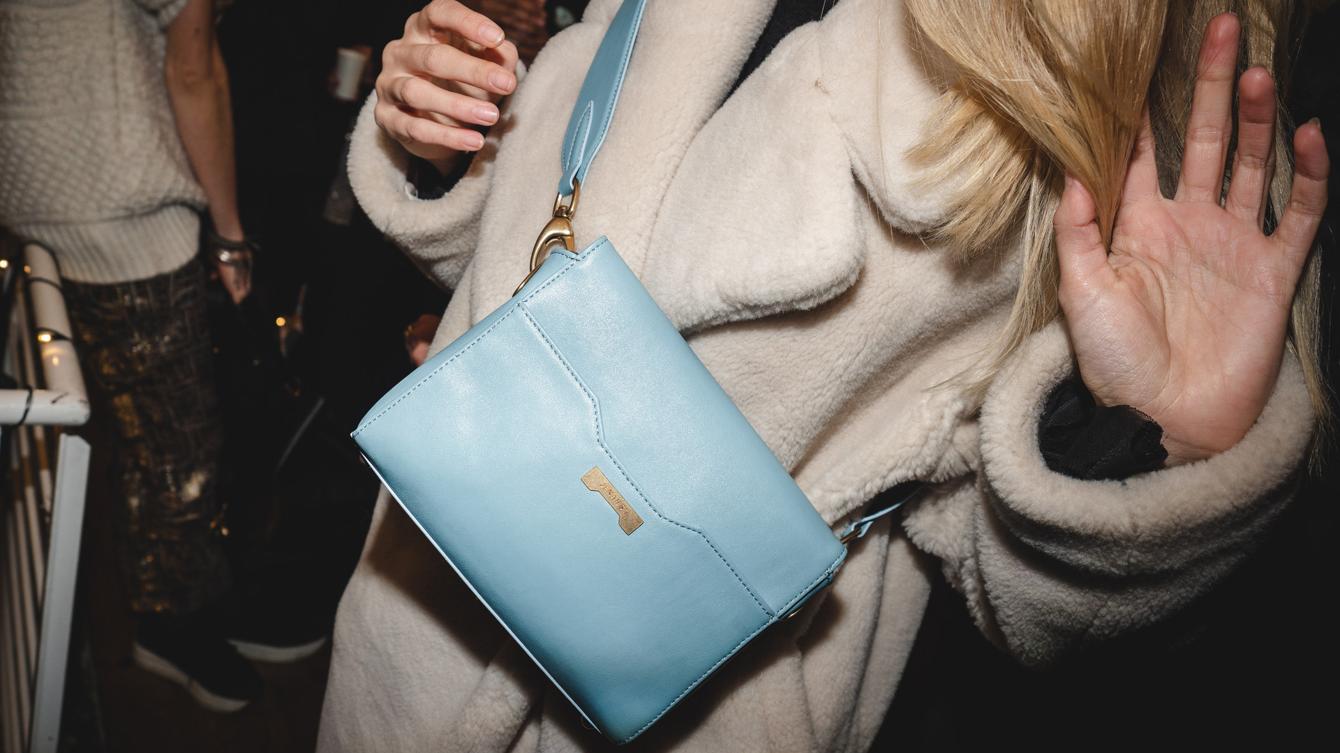 woman presenting a blue pouch during an event