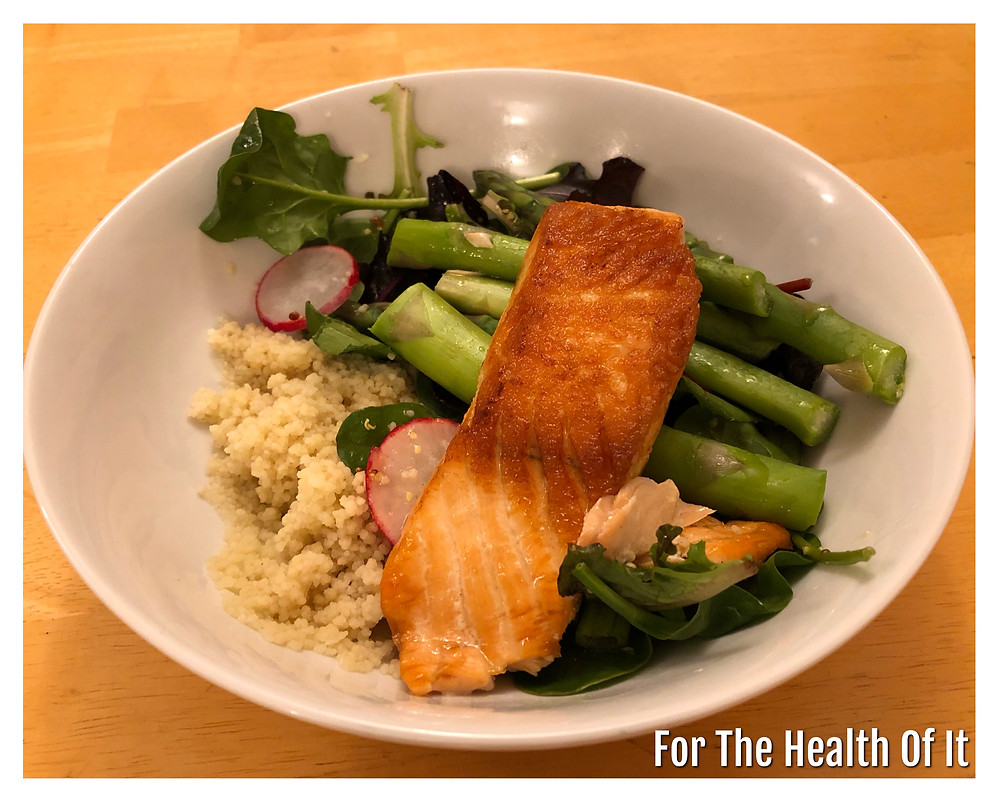 Salmon fillet on a bed of Cous Cous and Salad with a Mustard and Lemon Dressing