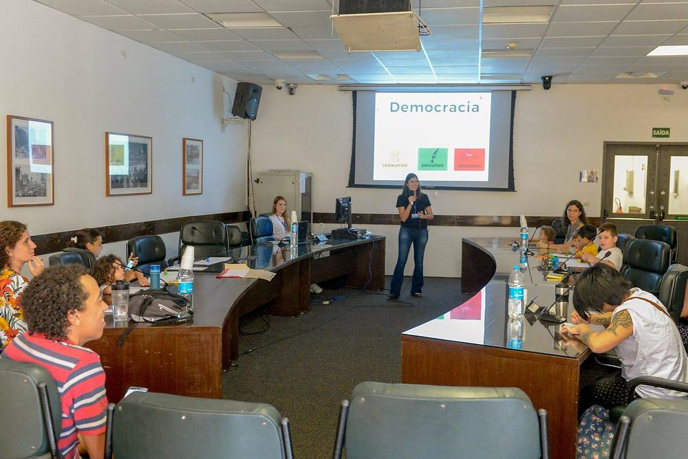 Mulheres e crianças em torno de uma mesa durante uma apresentação de slides. No slide está escrita a palavra Democracia